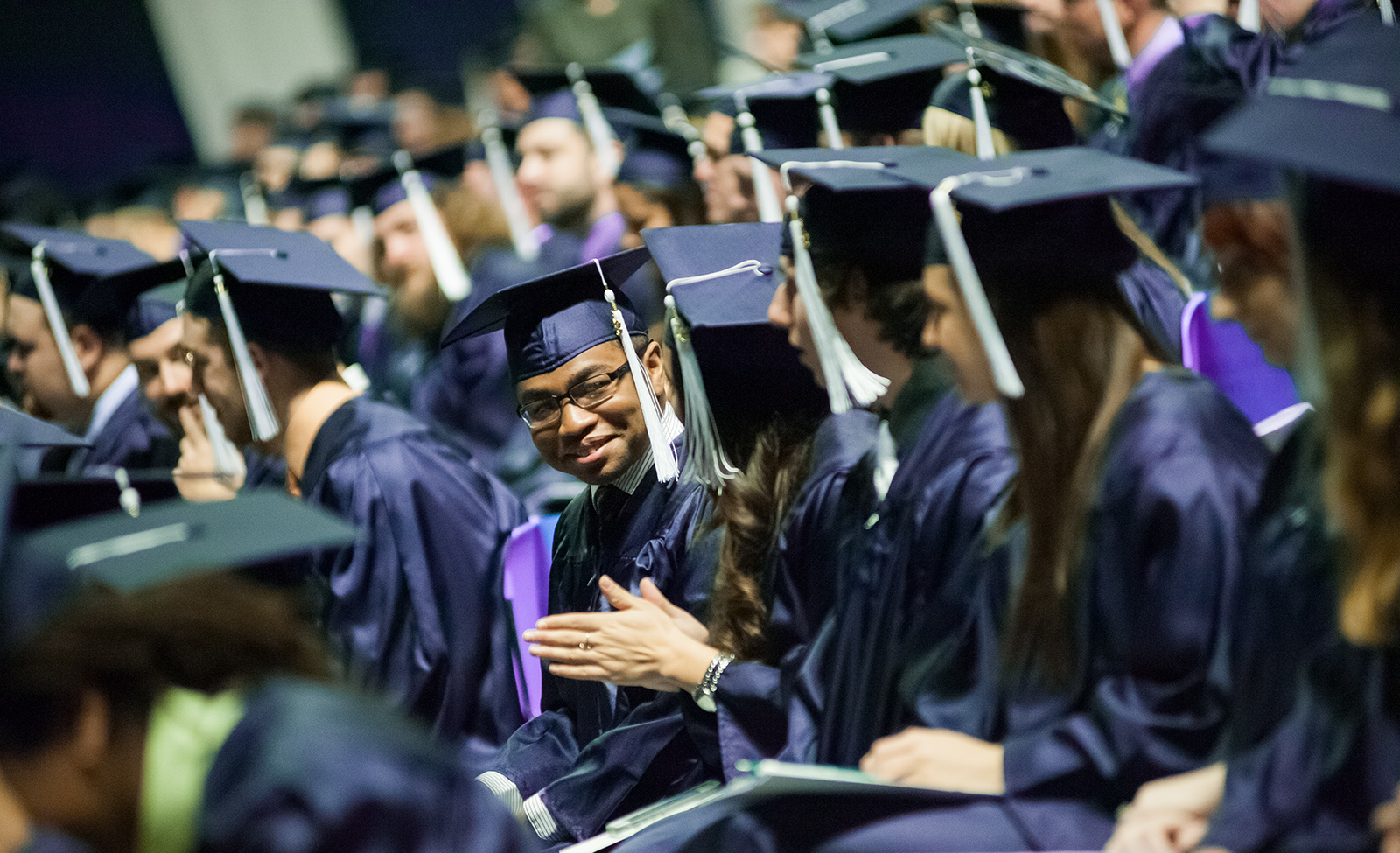 A Penn State graduate smiles at his peers during the commencement ceremony
